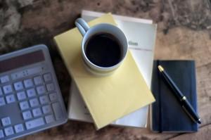 Tastatur neben einer Tasse Kaffee und Schreibblock